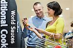 Couple choosing sauce in supermarket