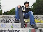 Teenage boy sat on steps with skateboard