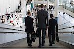 Three businessmen walking down stairs