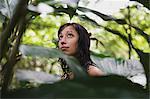 Young woman through foliage
