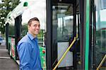 Portrait of happy mid adult man entering bus