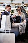 Senior couple checking bag after shopping at mall