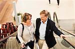 Happy senior couple on an escalator in shopping mall