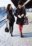 Happy female friends in warm clothing walking on station platform