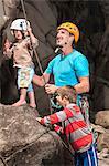 Man teaching children to rock climb