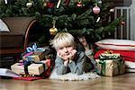 Boy laying under Christmas tree