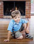 Smiling boy sitting on wooden floor
