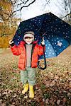 Boy in rain boots and umbrella in park