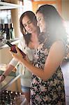Women reading vinegar bottle in grocery