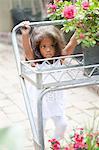 Girl pushing cart in plant nursery