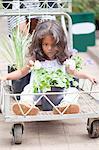 Girl sitting in cart at flower nursery