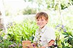Boy potting plants outdoors