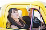 Woman admiring herself in car mirror