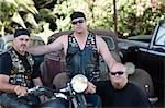Men sitting around motorcycle