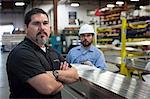 Worker standing in metal plant