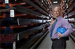 Businessman standing in metal plant