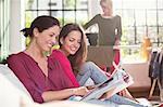 Women reading magazine together on sofa