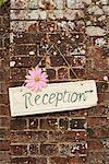 'Reception' sign on brick wall