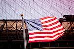 American flag waving by urban bridge