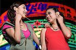 Girls sharing earphones