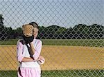 A girl hiding behind a baseball glove
