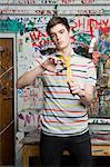 A teenage boy cutting tie in half