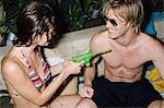 Woman pointing water pistol at man