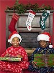 Siblings holding presents