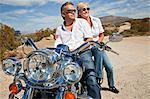 Senior couple wear sunglasses seated on motorcycle on desert road