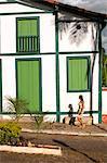 South America, Brazil, Goias, Pirenopolis, a woman walks past Portuguese colonial houses on the Rua Nossa Senhora do Rosario in the mining town of Pirenopolis near Brasilia