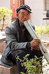 China, Yunnan, Xinping. An elderly man enjoying a peaceful smoke.