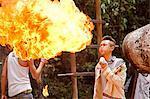 China, Yunnan, Xishuangbanna. A young man of the Jinuo ethnic minority group beathing fire, near Jinghong.