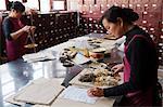 China, Yunnan, Kunming. Preparing medicines at Fu Lin Tang, the Old Pharmacy, which dates back to 1857, Kunming.