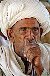 India, Rajasthan, Ajabgarh. A turbanned village man smokes a long pipe.
