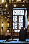 Turkey, Marmara, Istanbul, Yeni Mosque interior, man praying