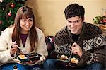 Couple eating microwave dinners on sofa