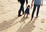 Couple helping toddler girl walk on beach