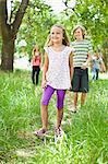 Children walking together in grass