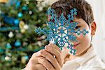 Boy holding blue snowflake decoration