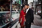 Couple window shopping on city street