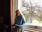 Girl reading by window
