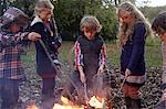 Children poking bonfire outdoors