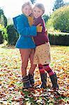 Girls hugging in autumn leaves