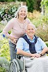 Older woman pushing husband's wheelchair outdoors