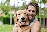 Smiling man petting dog outdoors