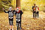 Children in skeleton costumes walking in park
