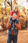 Older man carrying grandson on shoulders in park