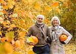 Older couple carrying pumpkins in park