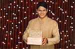 Man holding Diwali gift and smiling