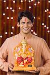 Portrait of a man holding an idol of lord Ganesha
